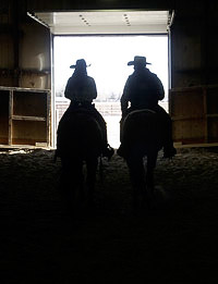 Silhouette of two riders through a door